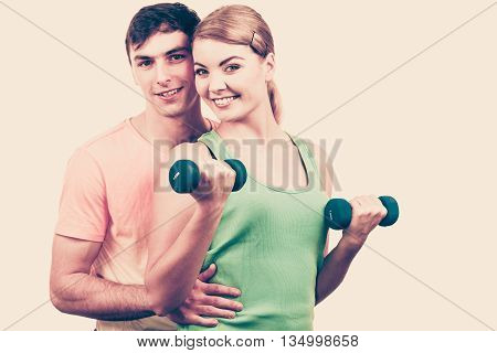 Couple fit woman and strong man exercising with dumbbells. Muscular guy and fitness blonde girl lifting weights. Bodybuilding.