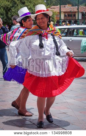 Peruvian Woman In Traditional Dresses Dancing On The Street In Cuzco, Peru
