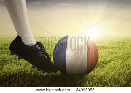 Soccer ball kicked by foot of football player at the field with sunlight background
