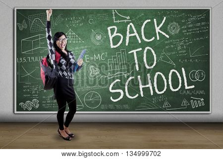 Portrait of cheerful female high school student standing in the class while raising hands with text Back to School on the chalkboard