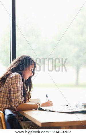 Portret van een serieuze jonge student het schrijven van een essay in een bibliotheek