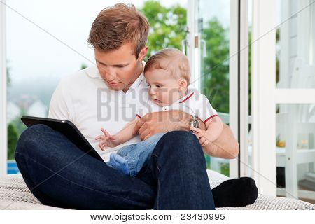 Father holding child while using digital tablet at home