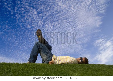 Young Man Lying Down On The Grass