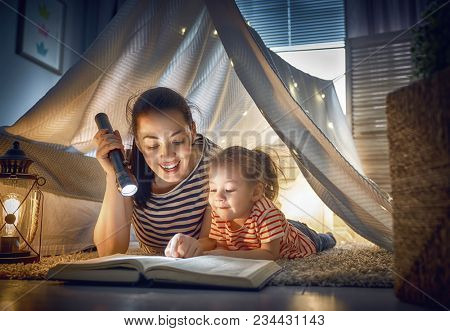 poster of Family bedtime. Mom and child daughter are reading a book in tent. Pretty young mother and lovely gi