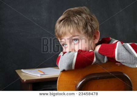 Student resting his head on his arms while looking up