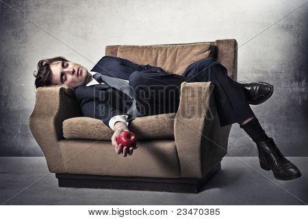 Asleep businessman lying on an armchair with an apple in his hand