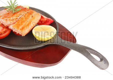 food: grilled salmon on iron pan over wooden plate isolated on white background