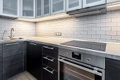 Interior Of Kitchen With Lighting. Modern Kitchen With Electric Stove And Oven. Black Induction Cook poster