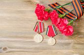9 May Card - Jubilee Medals Of Great Patriotic War With Red Carnations And St George Ribbon On The W poster