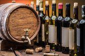 Wine bottles in row and oak wine keg. Wine background. poster