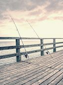 Several Fishing Rods Against The Wooden Railing Of The Beach Pier. Overcast Day, With The Hidden Sun poster