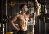 Sporty Man With A Rope. Photo Of Young Man With Perfect Body After Training. Strength And Motivation poster
