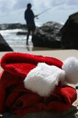 foto of boxing day  - Father Christmas on Boxing Day relaxing fishing after the busiest night of the year showing his hat clothes and a festive cocktail resting on the rocks and the ocean in the background