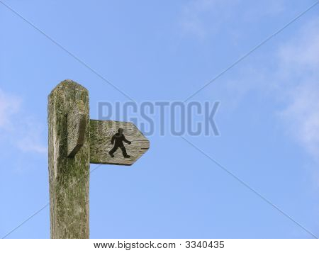 Signpost With Walking Man On Blue Sky