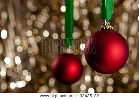 Two Red Christmas Baubles In Front Of A Gold Glitter Background
