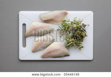 Fisch mit Kräutern auf dem Schneidebrett