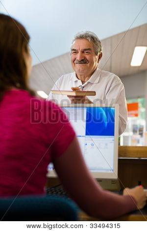 Girl And Senior Man Returning Book In Library