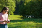 The Four-propeller Drone Hovered In The Air At Eye Level. In The Background, A Girl In Sunglasses An poster