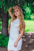 Portrait Of A Charming Blond Woman Wearing Beautiful White Dress Standing Under Fur Tree. poster