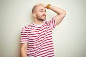 Young bald man with beard wearing casual striped red t-shirt over white isolated background smiling  poster