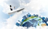 Funny Aviator Sitting In Paper Plane And Holding Steering Wheel. Pilot Driving Paper Plane In Cloudy poster