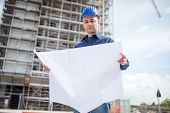 Site manager reading a blueprint in front of a construction site poster