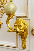 Golden door knocker in the shape of lion on a wooden door poster