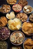 Salty snacks served as party food in ceramic bowls poster