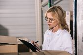 Concentrated Storekeeper In Glasses Writing On Clipboard In Warehouse poster