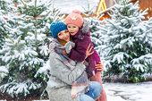 Cute Little Smiling Kid Girl And Mother On Christmas Tree Market. Happy Child, Daughter And Young Wo poster