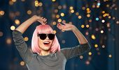 style, fashion and people concept - happy laughing young woman in pink wig and black sunglasses danc poster