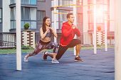 Fitness, Sport, Exercise, Lifestyle Concept. Mixed Race Young Man And Woman Doing Exercise On Street poster