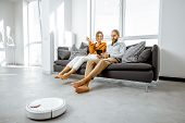 Young Couple Relaxing On The Couch While Automatic Vacuum Cleaner Doing The Housework In The Modern  poster