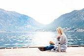 Woman Is Reading On Wooden Pier By Winter Sea, Beach, Mountains. Cozy Picnic With Coffee, Hot Bevera poster