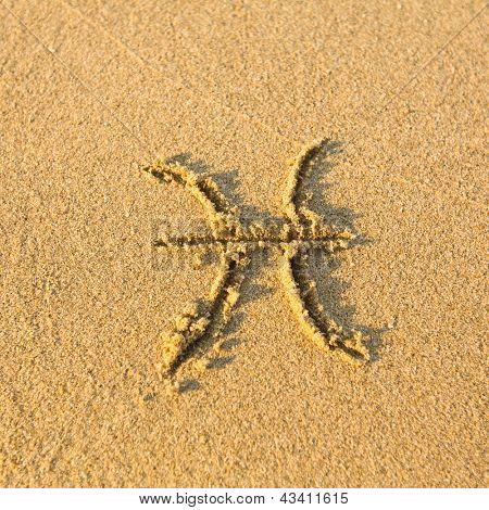 Zodiac sign Pisces, drawn on the facture beach sand. (zodiac signs series)