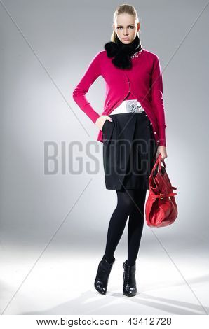 High fashion model with red bag posing on light background