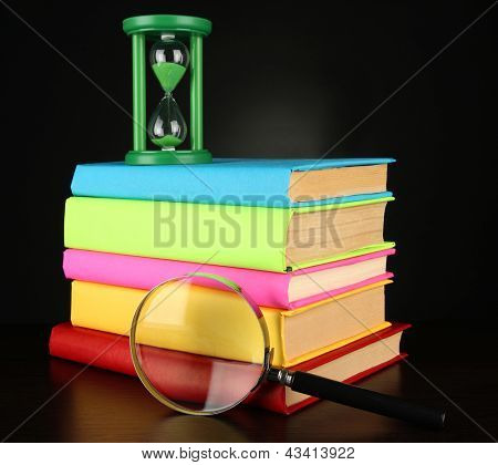 color books with magnifying glass on table on black background