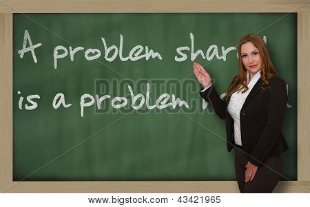 Teacher Showing A Problem Shared Is A Problem Halved On Blackboard