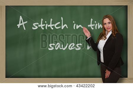 Teacher Showing A Stitch In Time Saves Nine On Blackboard