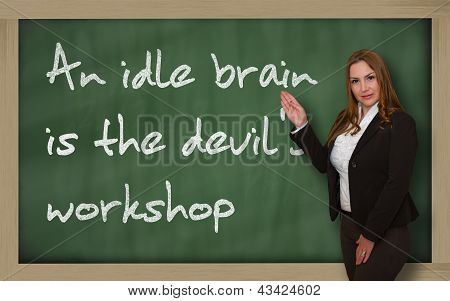 Teacher Showing An Idle Brain Is The Devil's Workshop On Blackboard