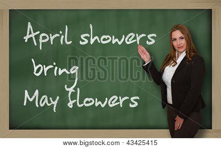 Teacher Showing April Showers Bring May Flowers On Blackboard