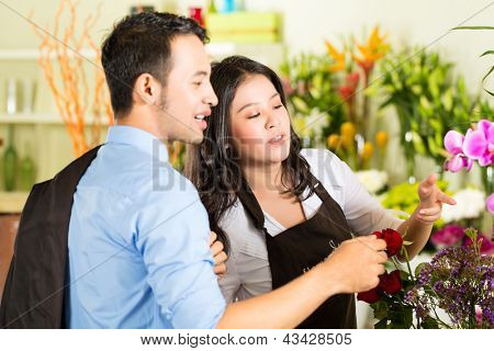 Friendly Asian florist or Saleswoman in a flower shop advising a customer