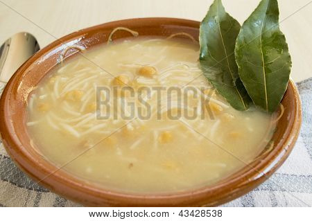 Bowl of chicken and chickpea soup with noodles and laurel
