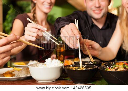 Young people eating in a Thai restaurant, they eating with chopsticks