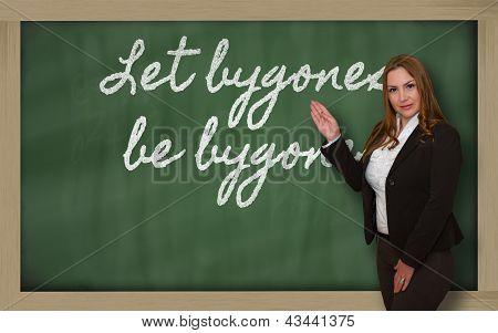 Teacher Showing Let Bygones Be Bygones On Blackboard
