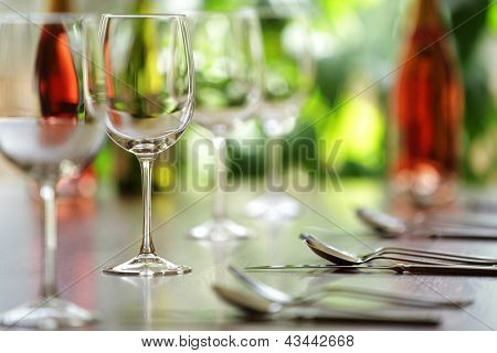 Restaurant table with cutlery, wine and wine glasses ready for a dinner party