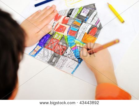 Childrens hand with pencil draws the house
