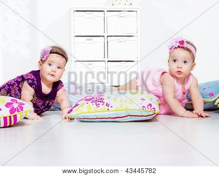 Adorable babies in dresses crawling