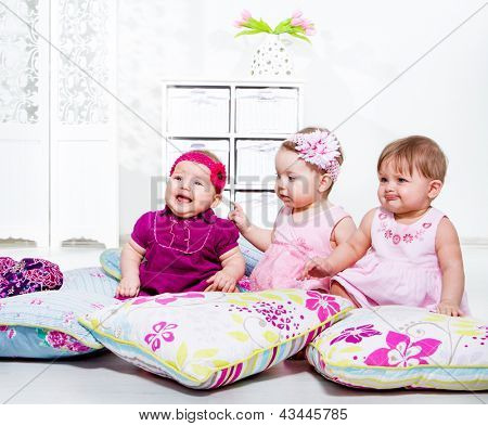 Three little kids sit on the floor among pillows