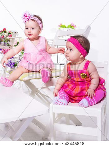 Two cute baby friends sitting